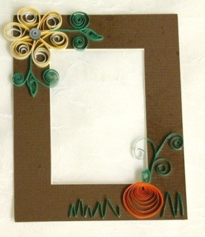 A hand quilled harvest frame with a flower and pumpkin.