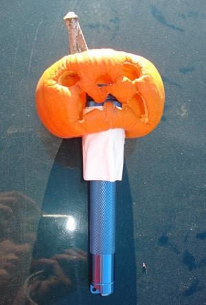 A mini pumpkin on a flashlight.