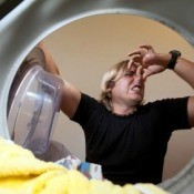 Stinky Laundry In Washing Machine with Man Holding Nose