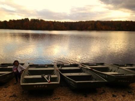 Child on lake shore near row boats.