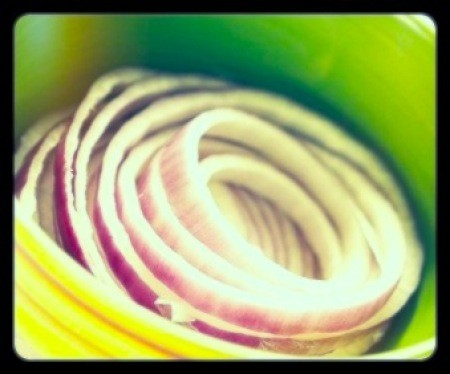 Slices of red onion in bowl.
