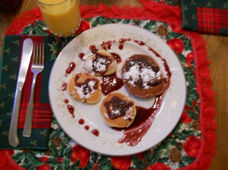 Pancakes with berry syrup and powdered sugar.