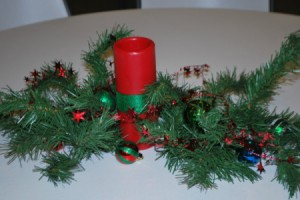 Red pillar candle with greenery for centerpiece.