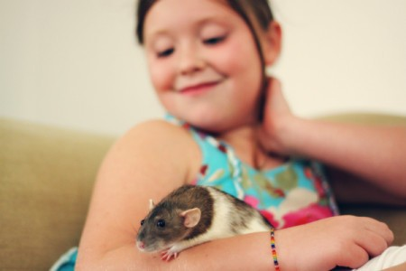 Gilr holding rat in arms.