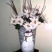 Floral bucket painted with a snowman and filled with white flowers.