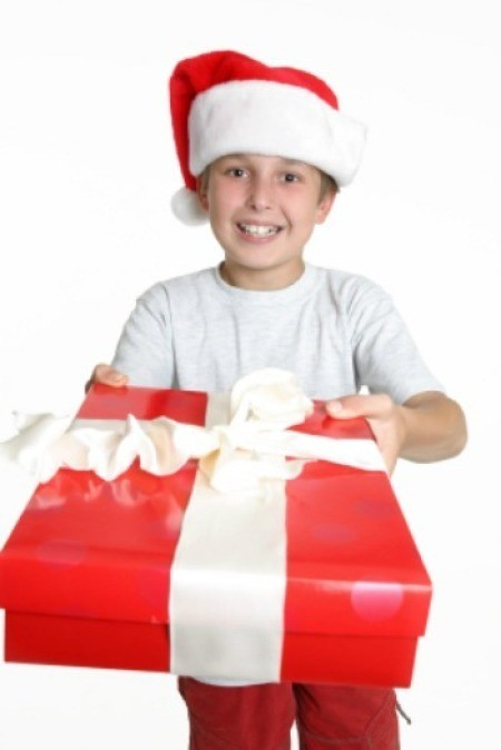 A boy with a Santa hat holding a large package.