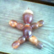 Man shaped decoration made from acorns.