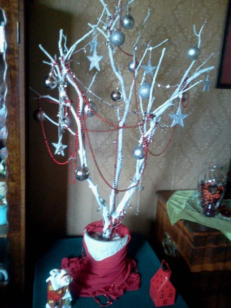Tree branch painted white and decorated with ornaments.