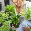 young woman kneeling down looking a plants