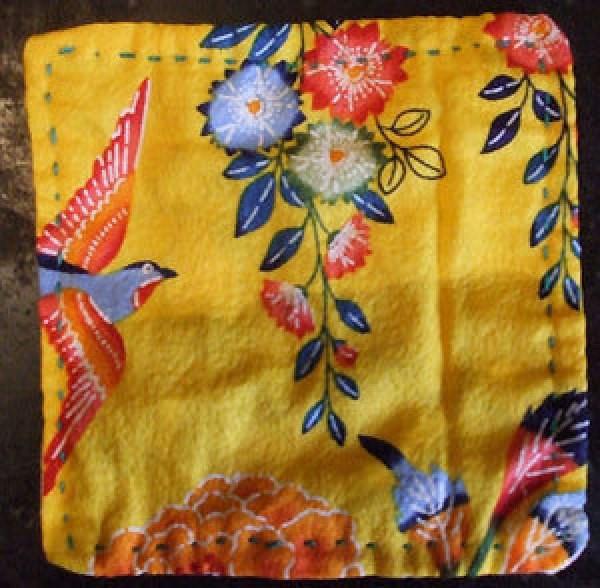 Fabric backing of ladybug sampler coaster.