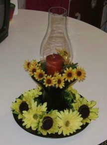 Hurricane candle holder decorated with silk flowers.