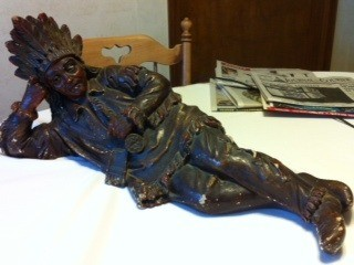 Statue of Native American lying on side with head propped up on hand.