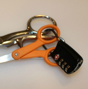 A lock attached to two pairs of nice scissors.