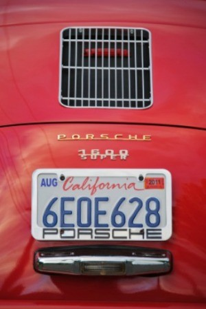 The rear license plate of a red car from California.