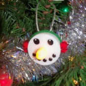 Snowman ornament with light-up nose.
