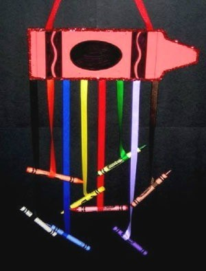 Large paper crayon with colored ribbons hanging from it with crayons glued to the ends.