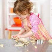 A toddler making cookies.
