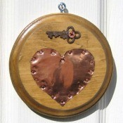 Copper heart on wooden circular plaque with a key attached above the heart.