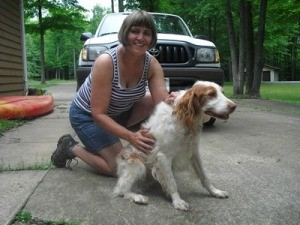 Woman in driveway with dog.