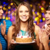 A 16 year old girl holding a cake at her birthday with friends.