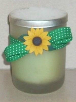 A container of bath salts with a sunflower button and green ribbon.