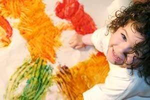 Little girl finger painting.