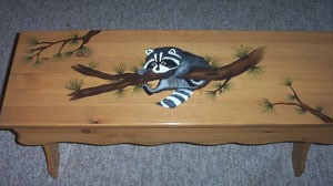 Bench decorated with a painted raccoon hanging onto a branch.