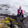 Boy sitting on rock on the shore.