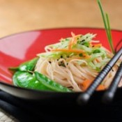 Red bowl filled with rice noodles toped with veggies.