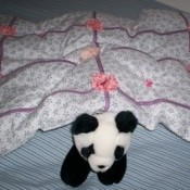 A small quilt covering a stuffed panda.