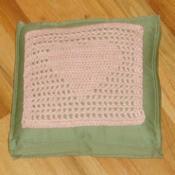 Pink filet crochet heart square on green pillow.
