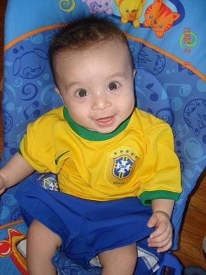 A cute baby boy in a bouncy seat.