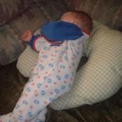 A baby sleeping on a handmade Boppy pillow.