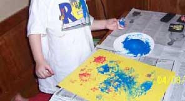 Child making print art.