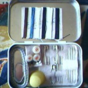 A sewing kit inside an empty Altoid's tin.