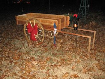 Wooden wagon with large red bow on wheel.