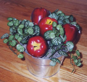 Apples and faux greenery in pail