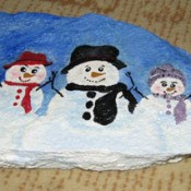 Rock painted with three snowmen.