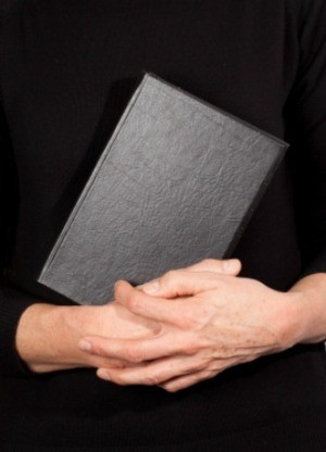 A pastor holding a bible.