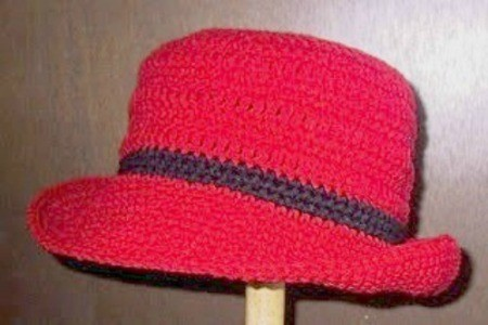 Closeup of a red crochet hat with brim.