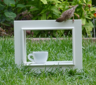 A sparrow on a white frame outside in the grass, with a teacup.