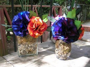 two vases with blue and purple flowers with one red and  yellow one also