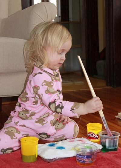 Little girl painting cake.