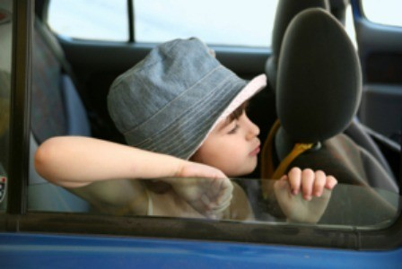 Kid riding in a car.