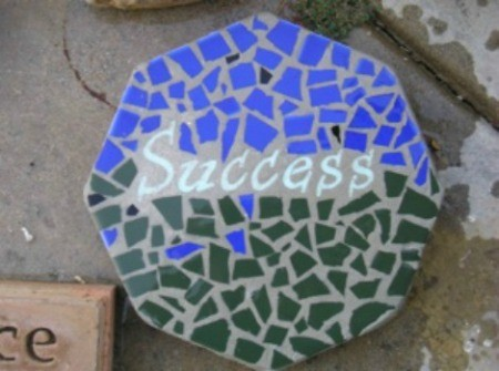 "Mosaic Stepping Stone - using blue and green pieces and the word ""Success"" in center"