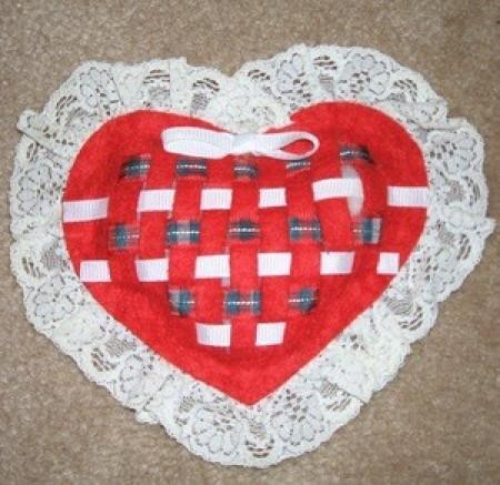A woven felt sachet in the shape of a heart.