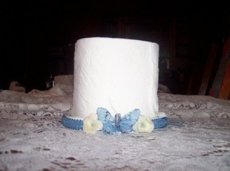 CD Spindle Toilet Paper Holder - TP on holder decorated with blue ribbon, faux flowers and a small butterfly