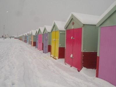 Multicolored huts in the snow.