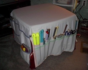Fabric table cover with pockets for organizing craft supplies and tools.