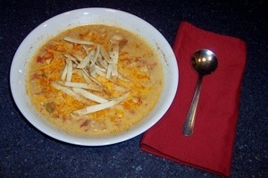 A bowl of Chicken Tortilla Soup next to a napkin and spoon.